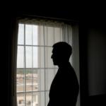 Man Standing Alone by Window