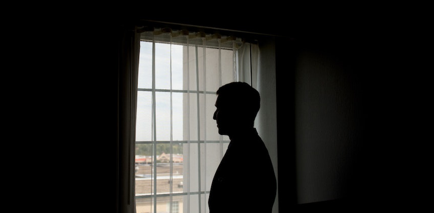 Man Standing Alone by Window