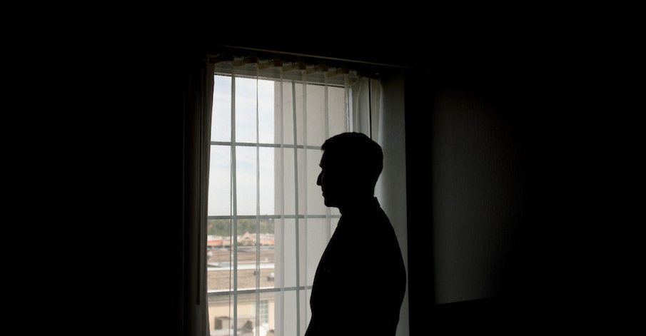 Immigrant Man Standing Alone by Window
