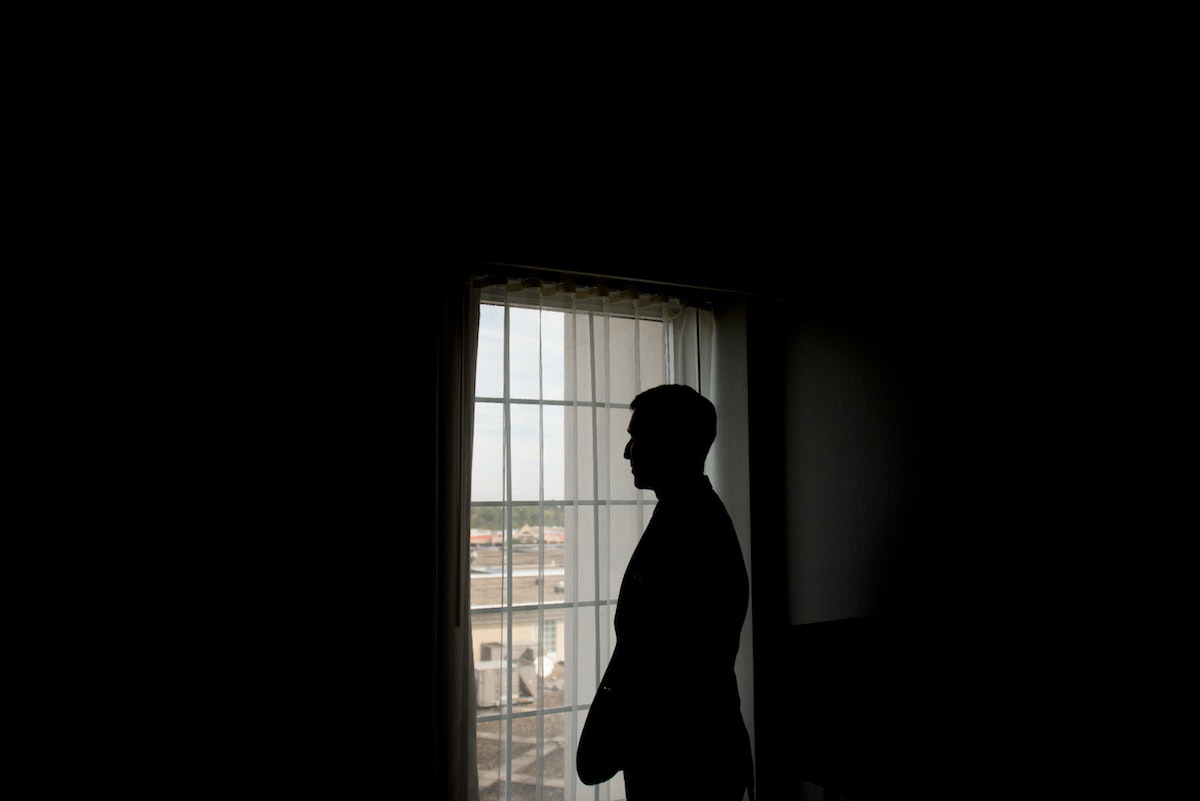 Immigrant Standing Alone by Window
