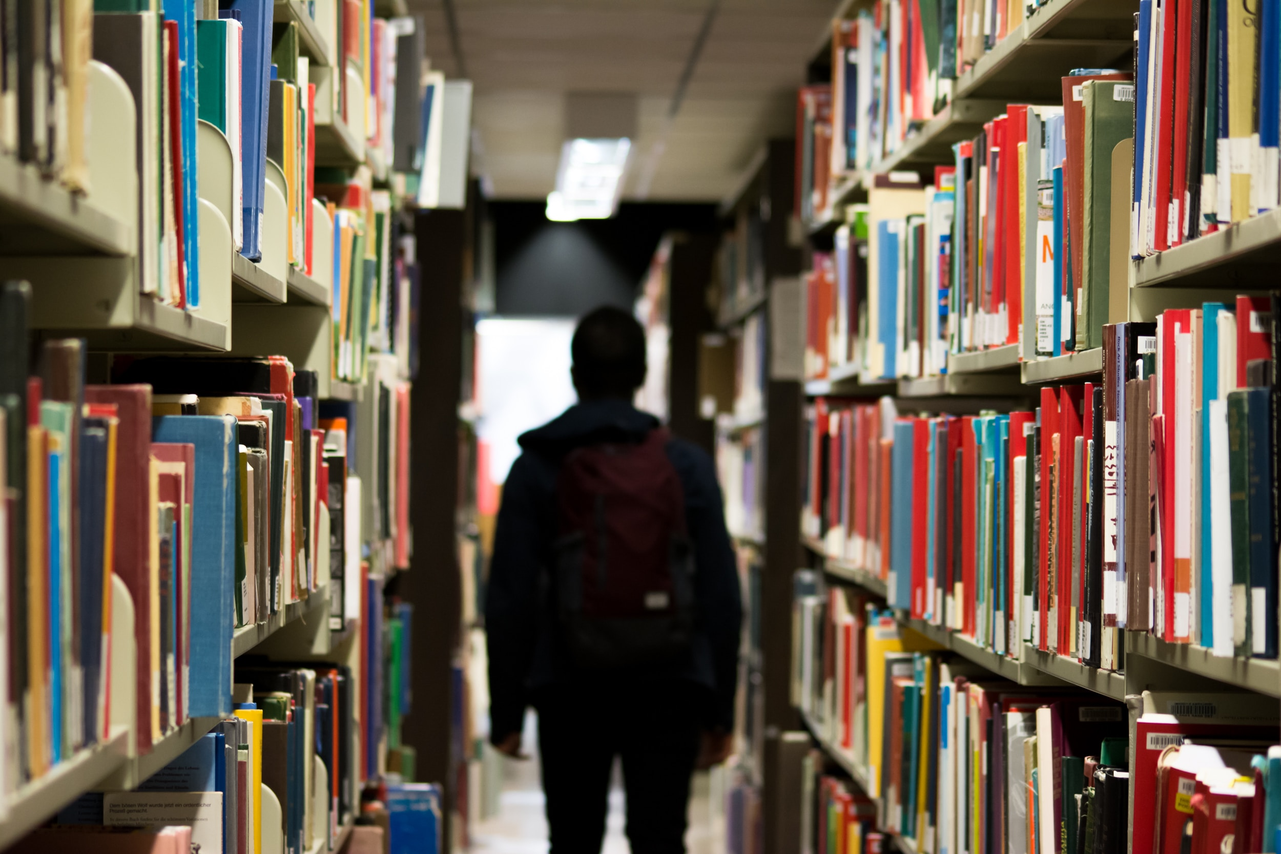 International student walking in a library.