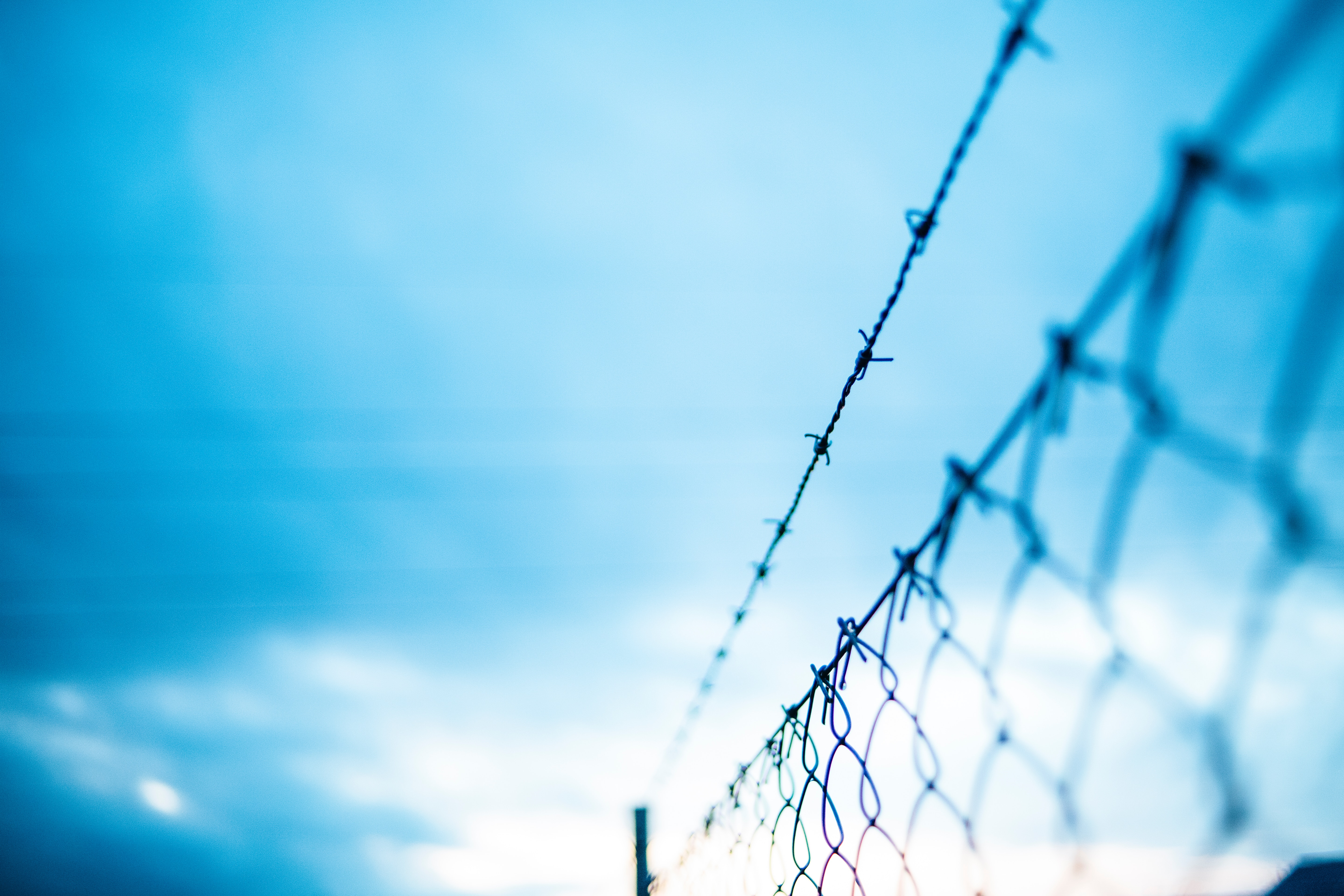 A barbed wire fence set against a cloudy sky.