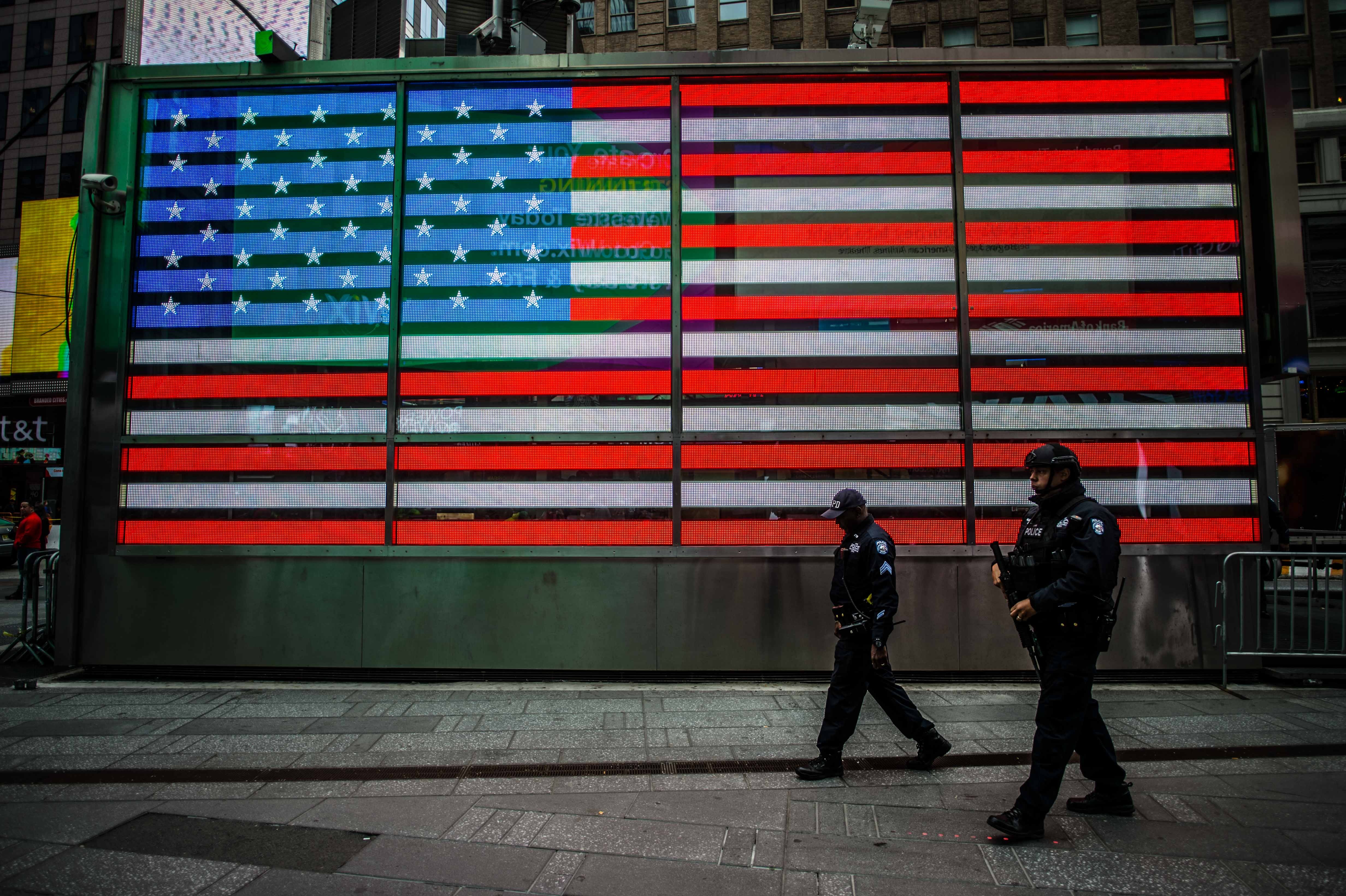 Police officers walking past an American flag.