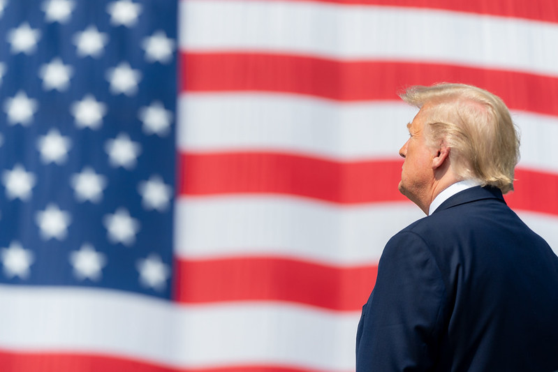 President Donald Trump stands in front of an American flag.