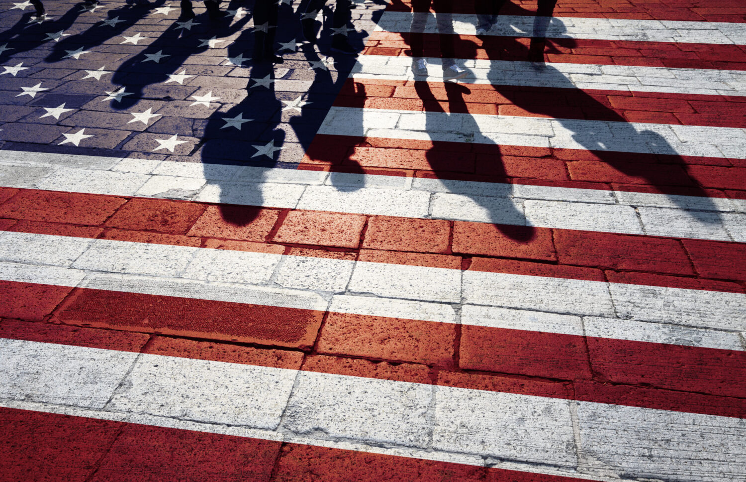 U.S. immigrant Shadows on a flag-painted paved street