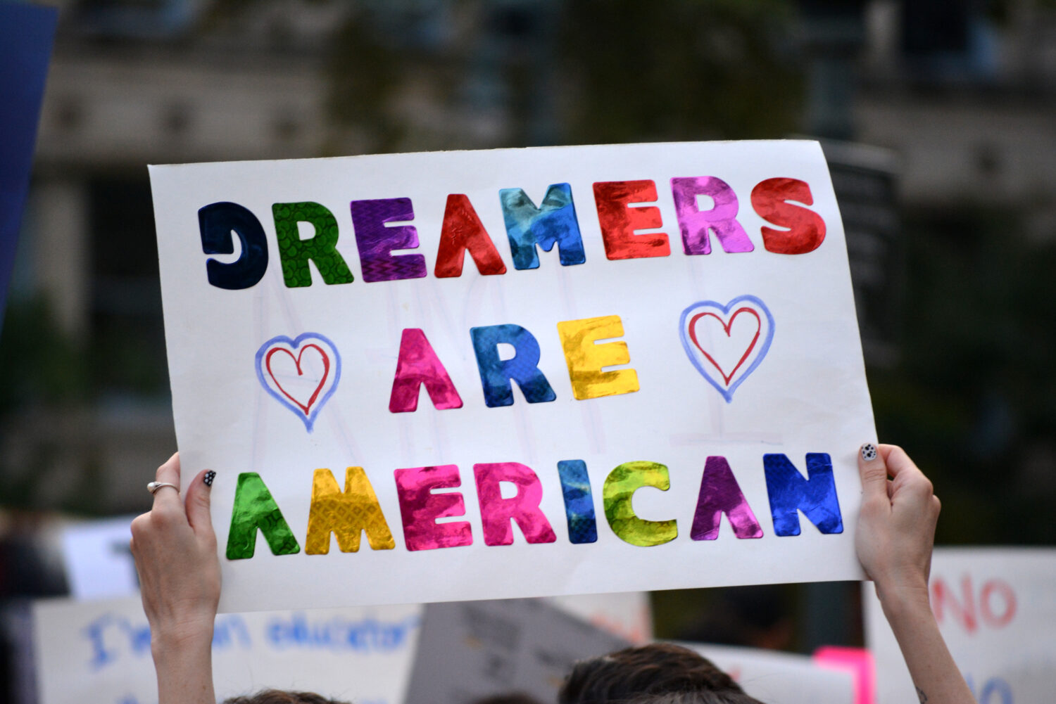 DACA protester with sign: Dreamers Are American